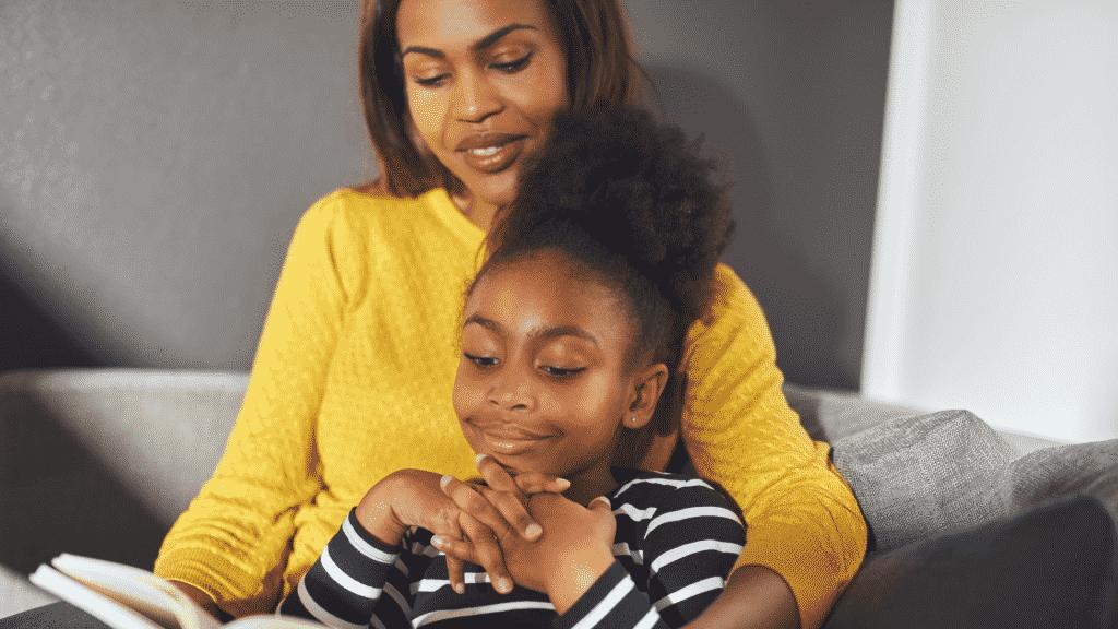 Mãe com a filha no colo lendo um livro para ela