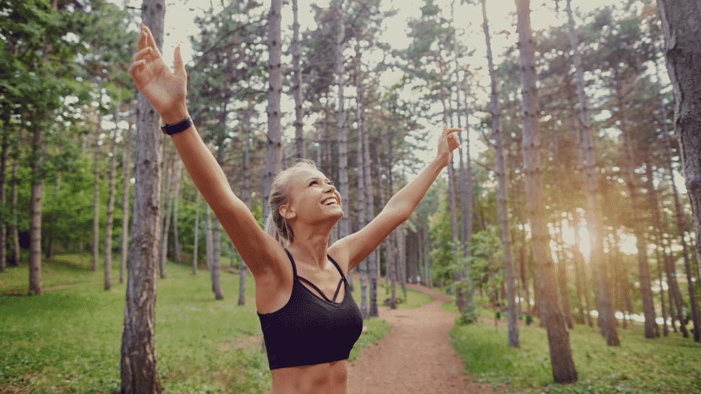 Mulher sorrido com os braços erguidos na floresta depois de correr
