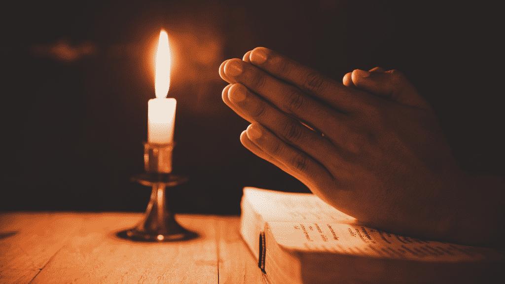 Pessoa rezando sobre bíblia com vela acesa
