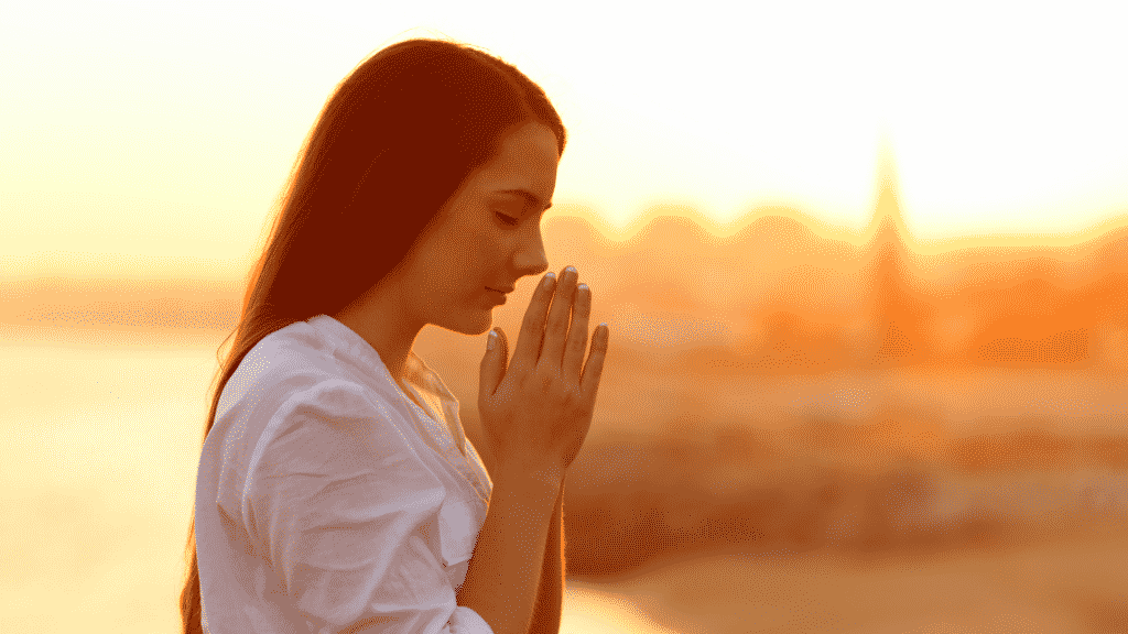 Mulher orando e agradecendo durante o por do sol