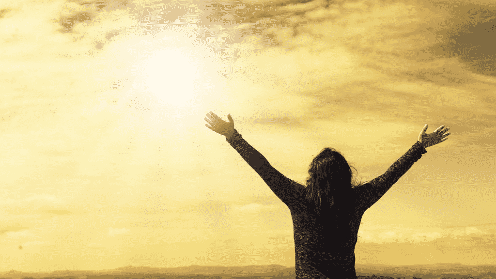 Mulher com os braços erguidos para o céu