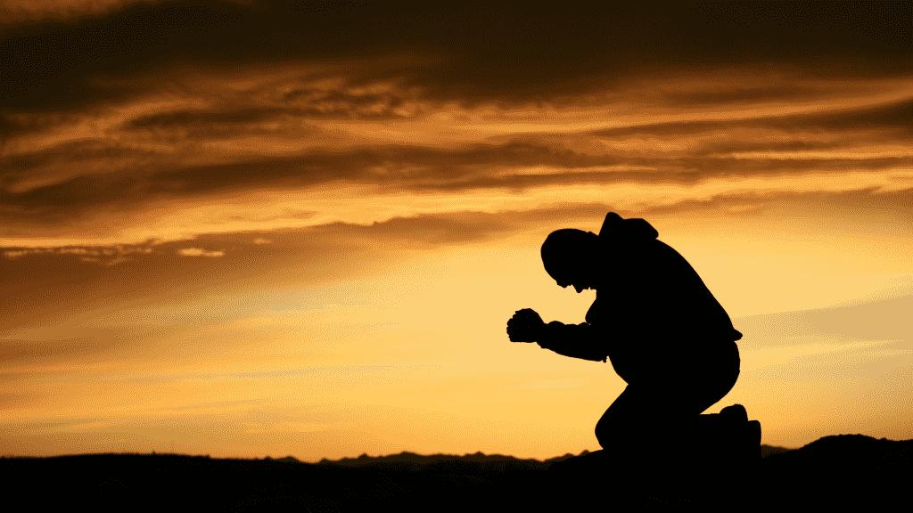 Silhueta de homem ajoelhado orando sob o por do sol