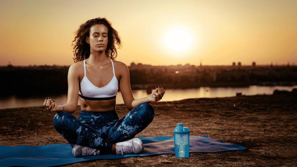 Mulher meditando na frente do lago