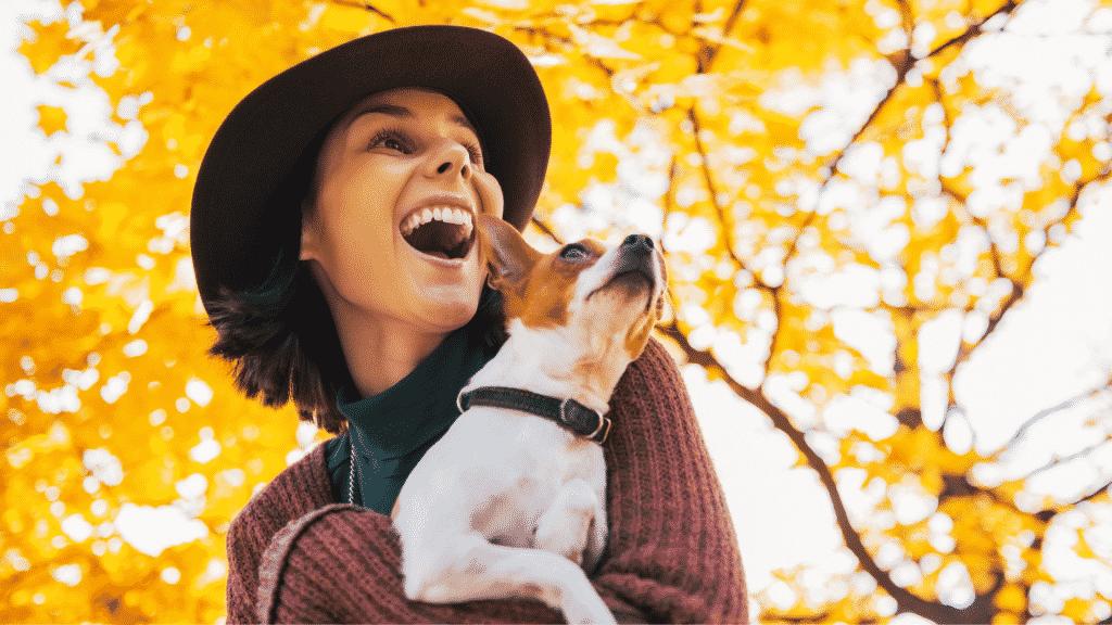 Mulher sorridente com o seu cachorro no colo