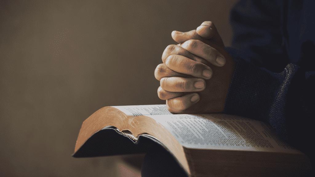 Homem com as mãos juntas orando sobre bíblia aberta