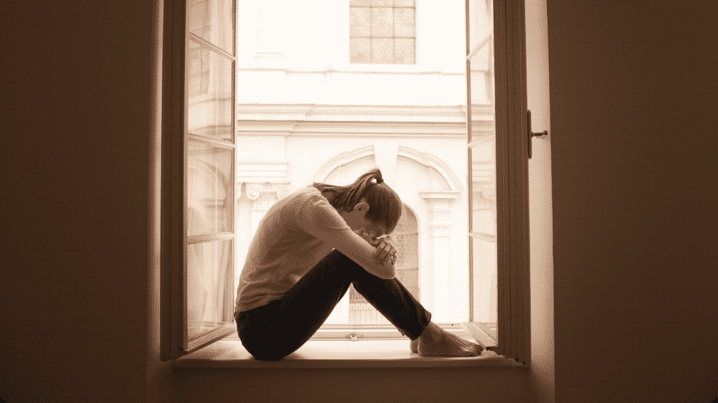 Mulher triste com o rosto sob os joelhos sentada na janela