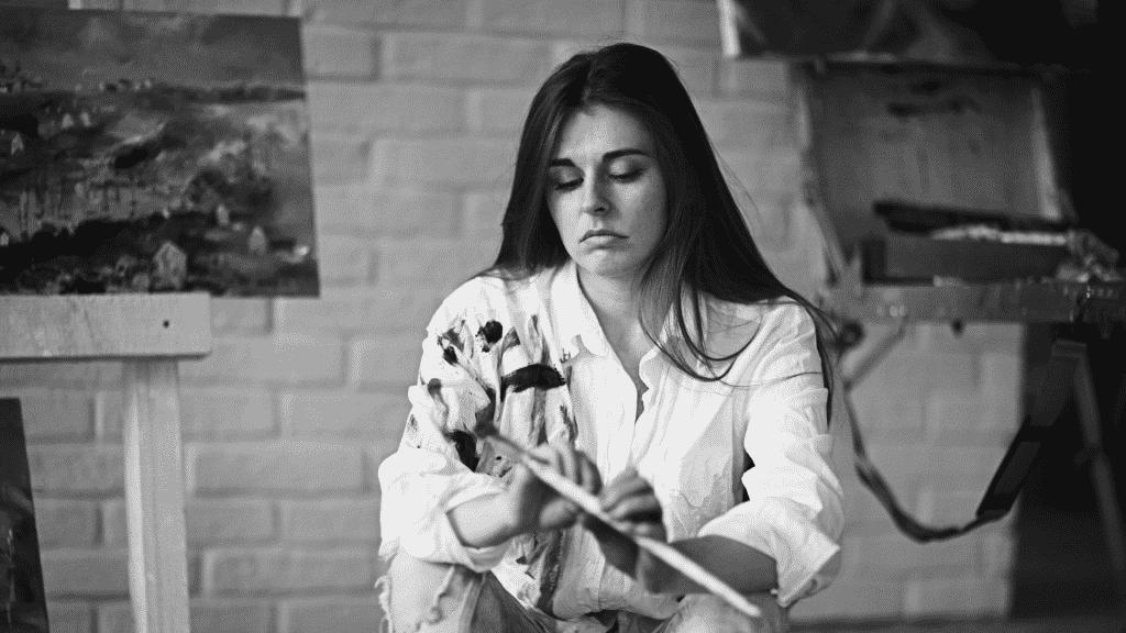 Mulher artista triste pintando quadro