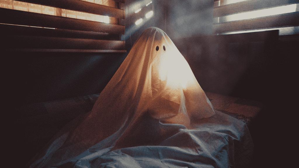 Fantasma de lençol sentado sobre cama