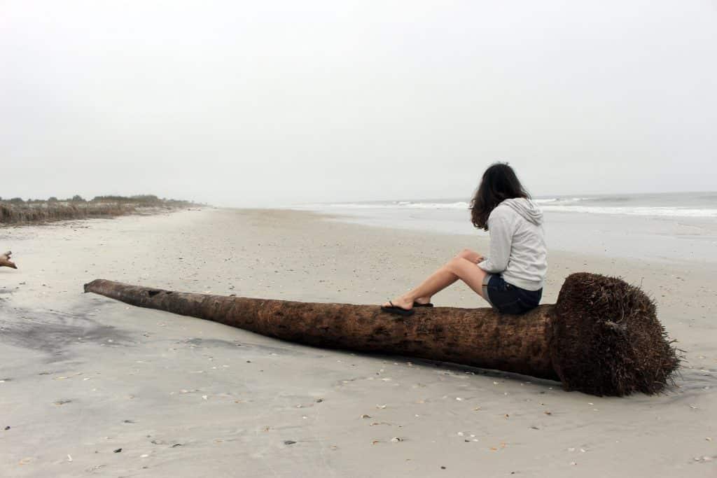 Mulher branca sentada no tronco de uma árvore na praia.