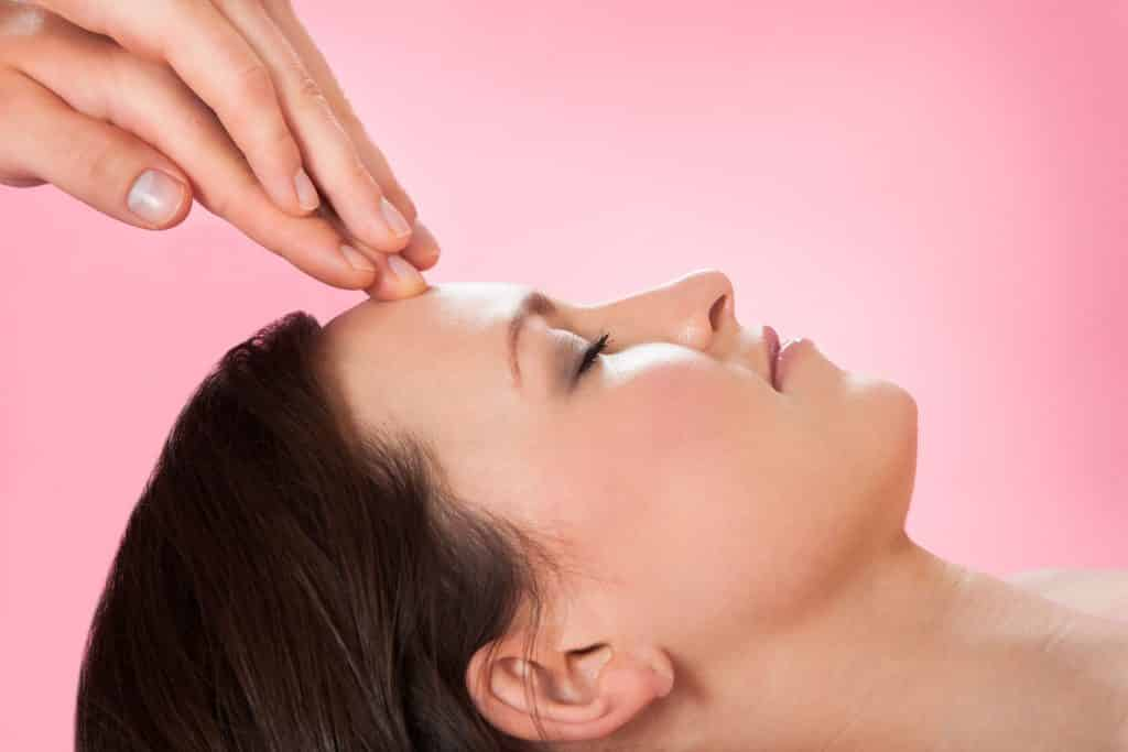 Perfil de mulher branca recebendo massagem na testa.
