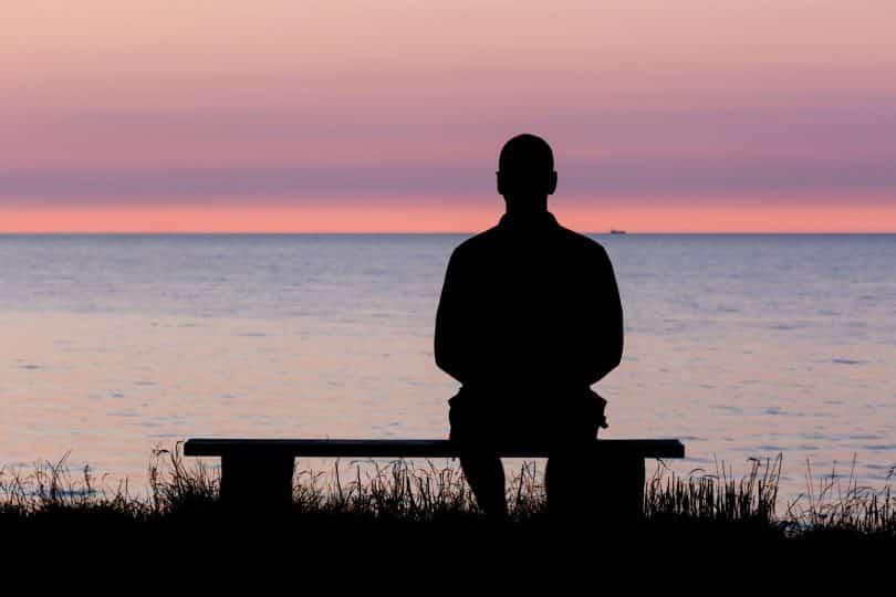 Homem sentado em banco à beira de lago observa o pôr do sol.