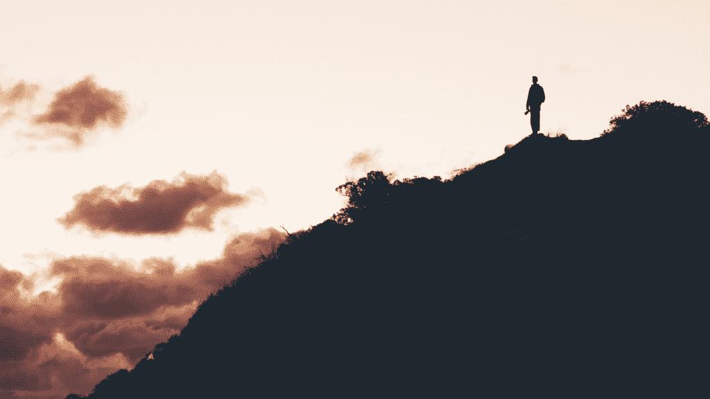 Silhueta de pessoa no topo da montanha observando o céu