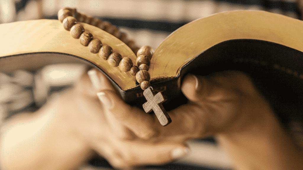 Pessoa lendo a bíblia com rosário