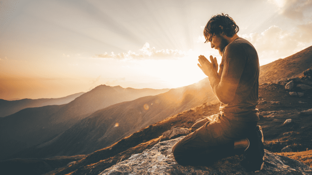 Homem orando sobre o topo da montanha sob o por do sol