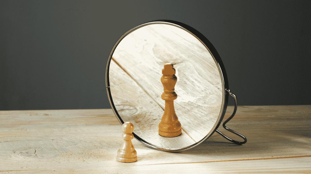 Representação do ego com um peão de xadrez vendo o reflexo como uma rainha