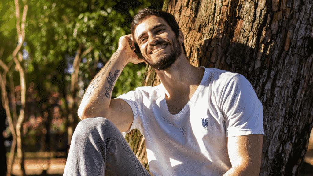 Homem sorridente sentado embaixo de uma árvore