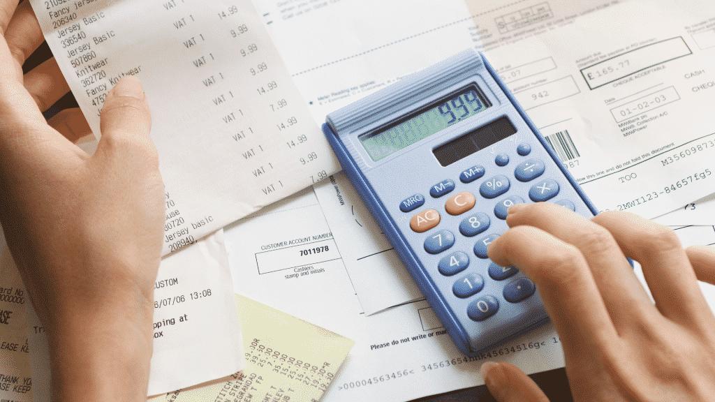 Pessoa fazendo calculo de dinheiro na calculadora