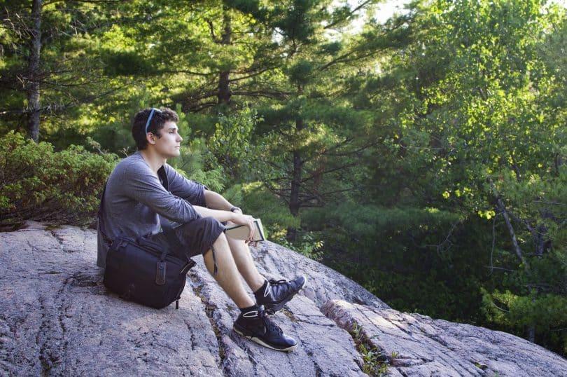 Homem sentado em pedra em ambiente externo e arborizado. Ele está com os braços nos joelhos.