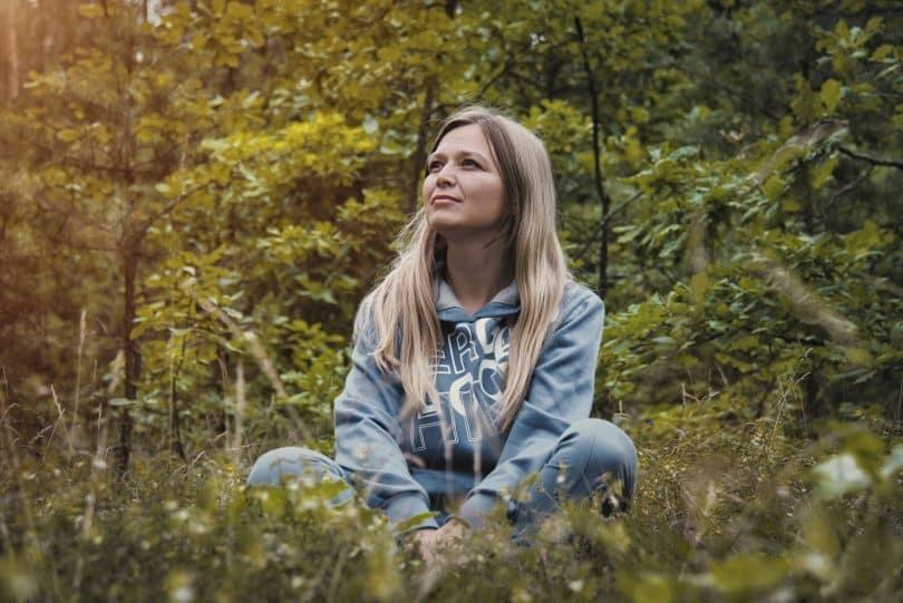 Mulher branca e loira sentada na grama.