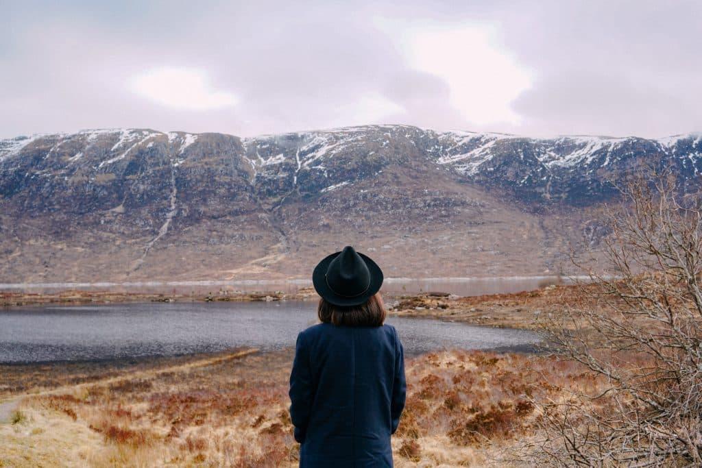 Mulher de costas próxima às montanhas e rio.