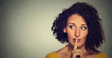 Mulher olha para o lado e coloca o dedo indicador sobre os lábios, indicando silêncio