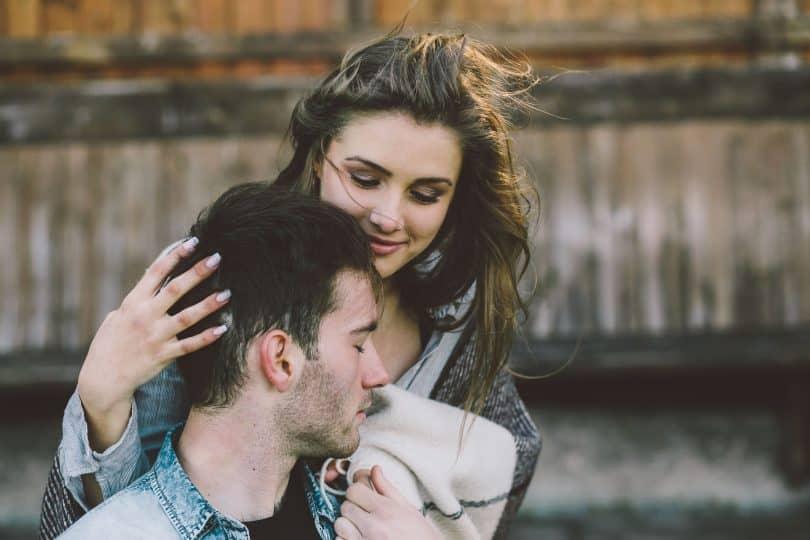 Homem e mulher brancos abraçados.