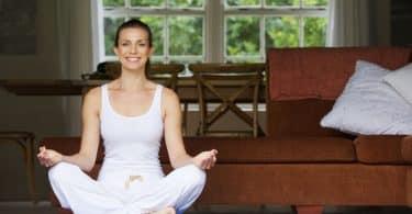 Mulher sentada no chão de casa em posição de lótus