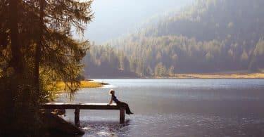 Homem sentado à beira de píer. O cenário é arborizado.