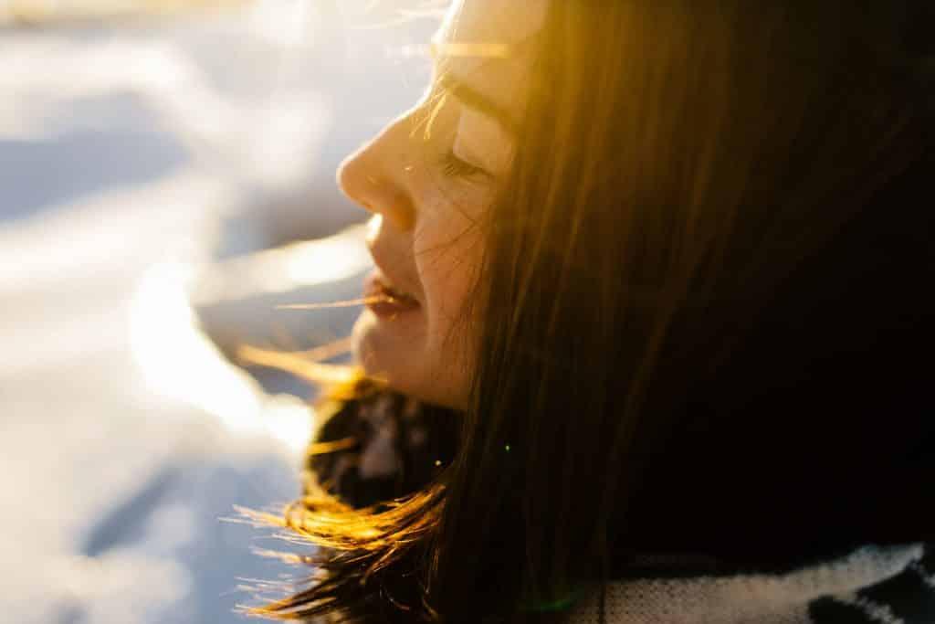 Mulher branca de olhos fechados sendo iluminada pela luz do sol.