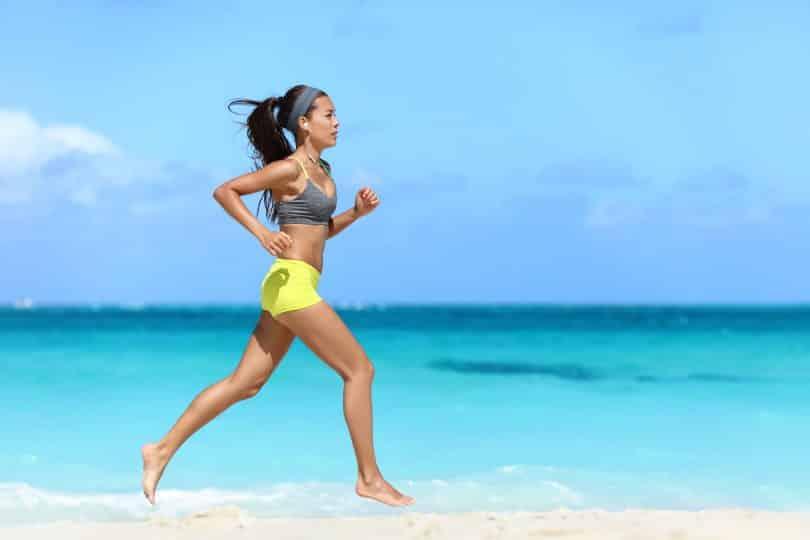 Mulher corre em praia, à beira mar.