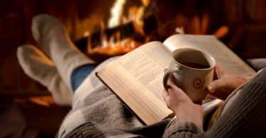 Pessoa com livro aberto sobre o colo, ela segura uma caneca. Ao fundo, há uma lareira.