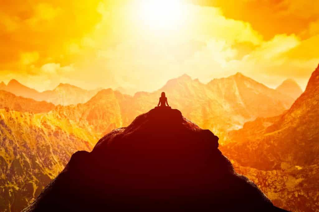 Mulher meditando em posição sentada de ioga no topo de uma montanha acima das nuvens ao pôr do sol.