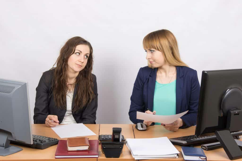 Mulheres brancas num escritório se estranhando.