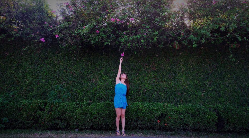 Mulher branca na ponta do pé pegando uma flor na árvore.