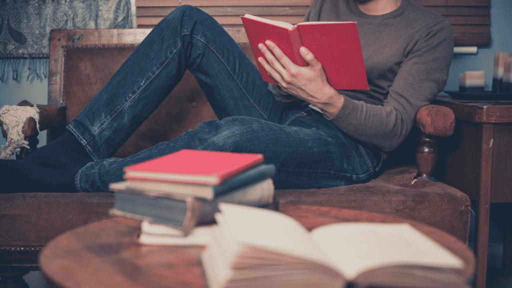 Pessoa lendo livros deitada no sofá