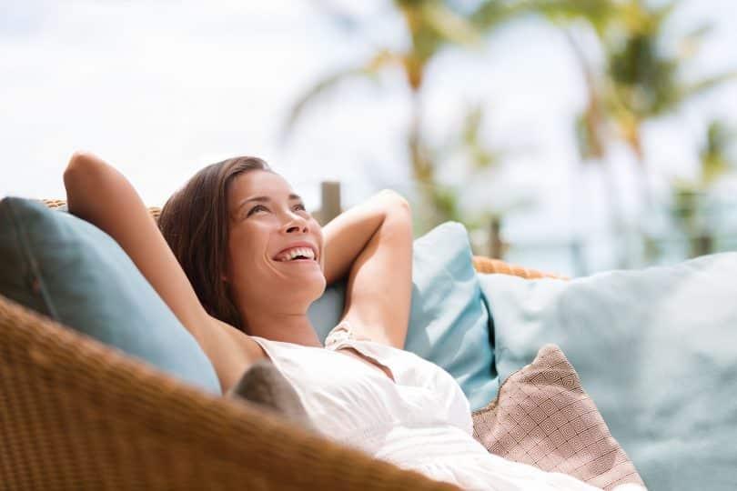 Mulher sentada em sofá em área externa sorri e olha para cima. Ela está deitada sobre as mãos.
