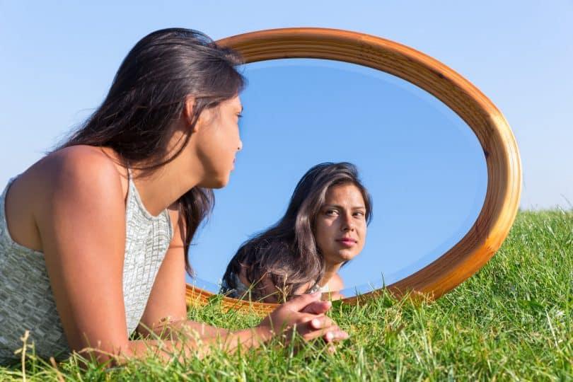 Mulher deitada de bruços na grama observa seu reflexo em espelho.