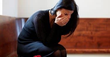 Mulher chora com as mãos sobre o rosto. Ela está sentada em um banco.