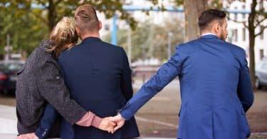 casal sentado no banco e se abraçando enquanto a mulher de mãos dadas com outro homem