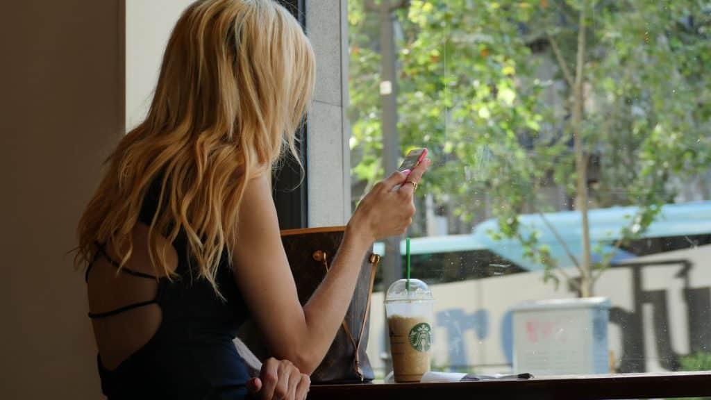 Mulher branca loira segurando celular.