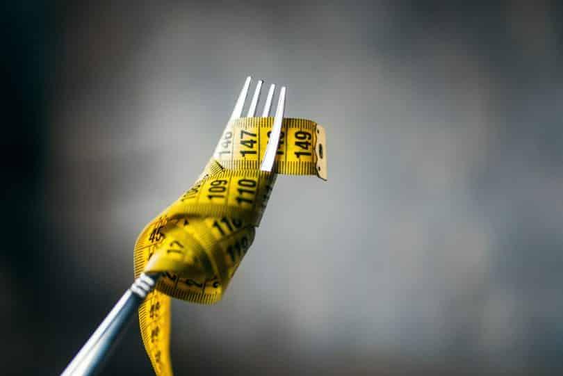 Fita métrica em torno de garfo.
