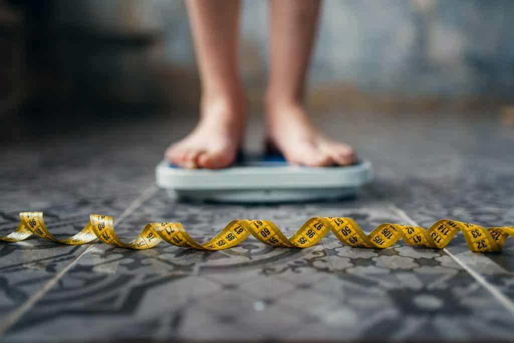 Mulher branca numa balança e fita métrica amarela no chão.