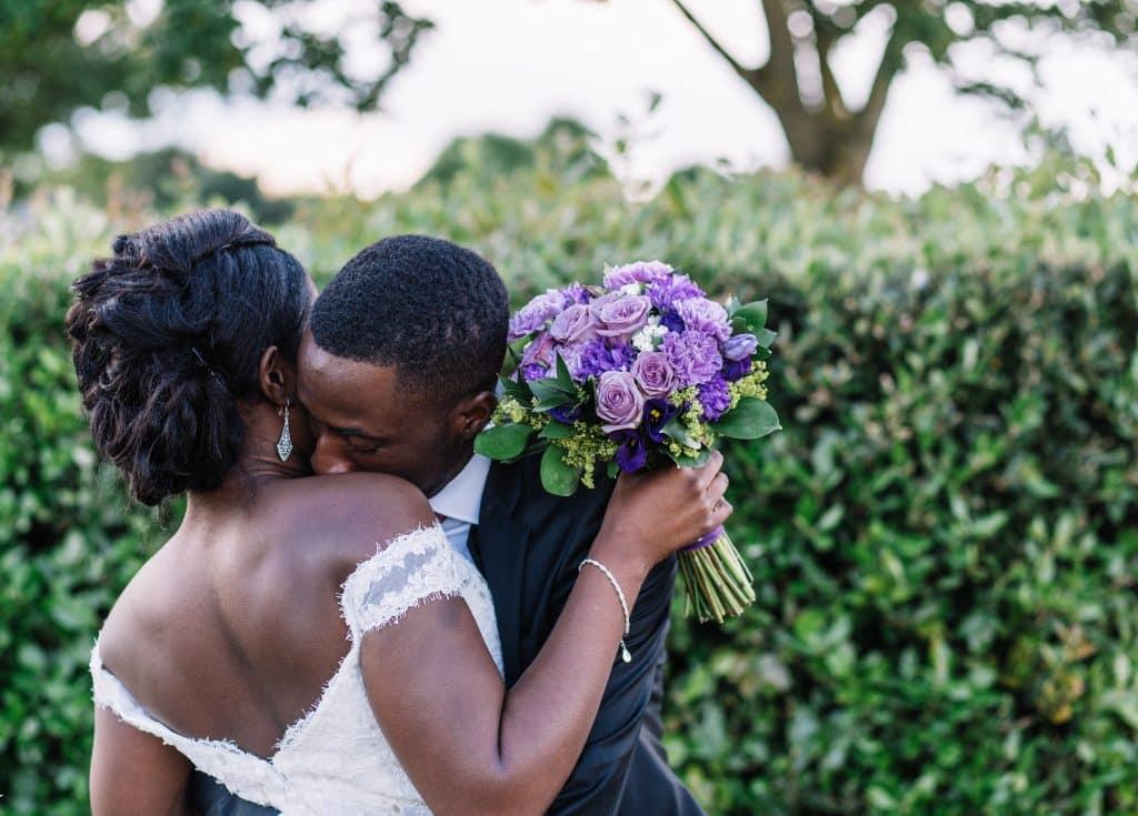 Homem e mulher negros abraçados no casamento.