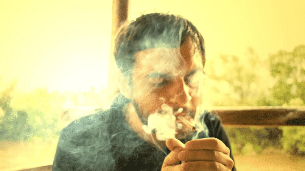 Imagem de um homem fumando um cigarro de maconha