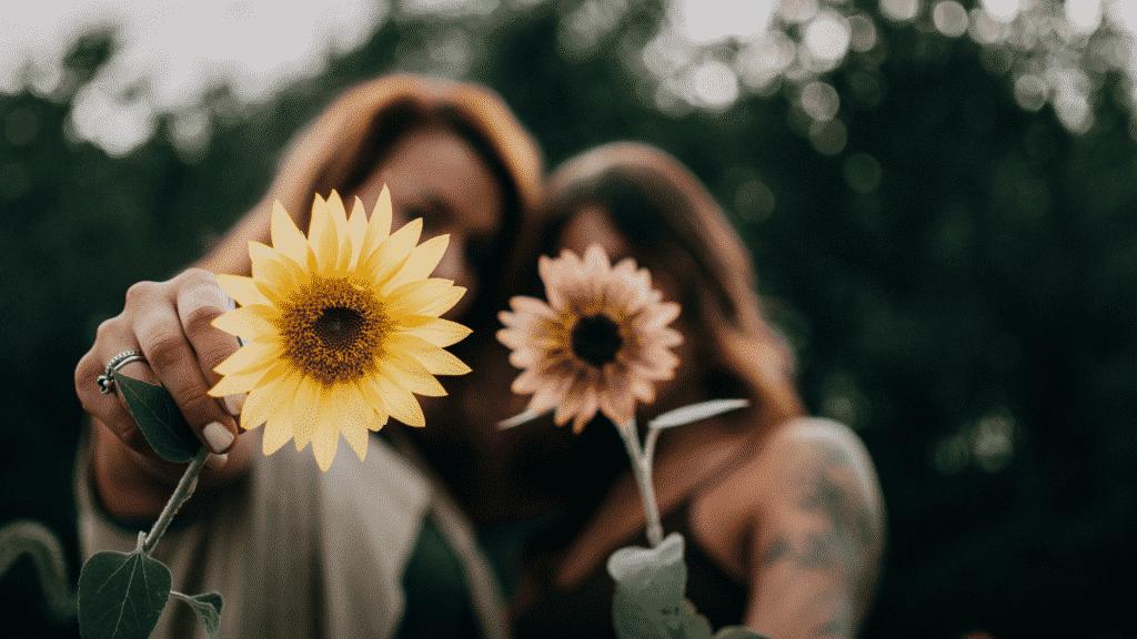 Duas amigas segurando flores em frente à câmera