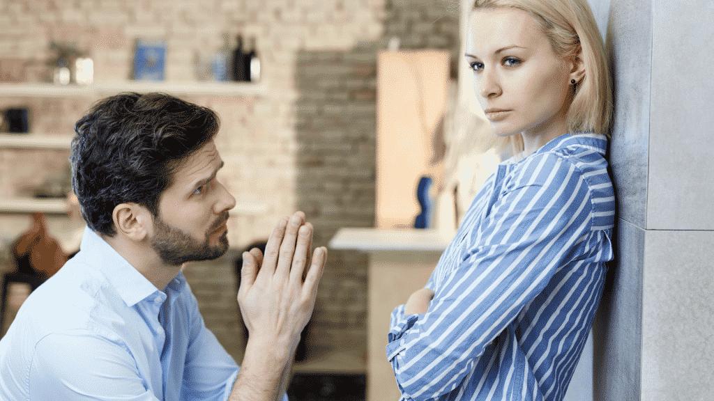 Homem pedindo perdão ajoelhado para mulher