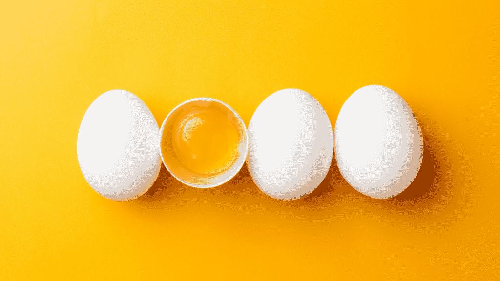 Imagem de uma sequência de 4 ovos. Um deles está partido ao meio com a gema em evidência