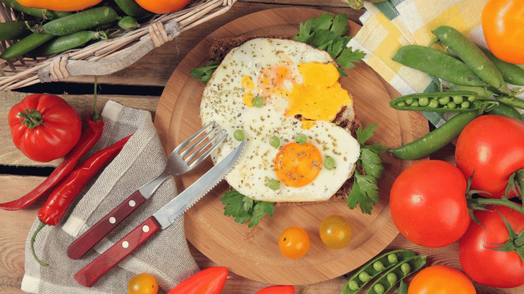 Prato com ovos fritos em cima de uma mesa repleta de vegetais.