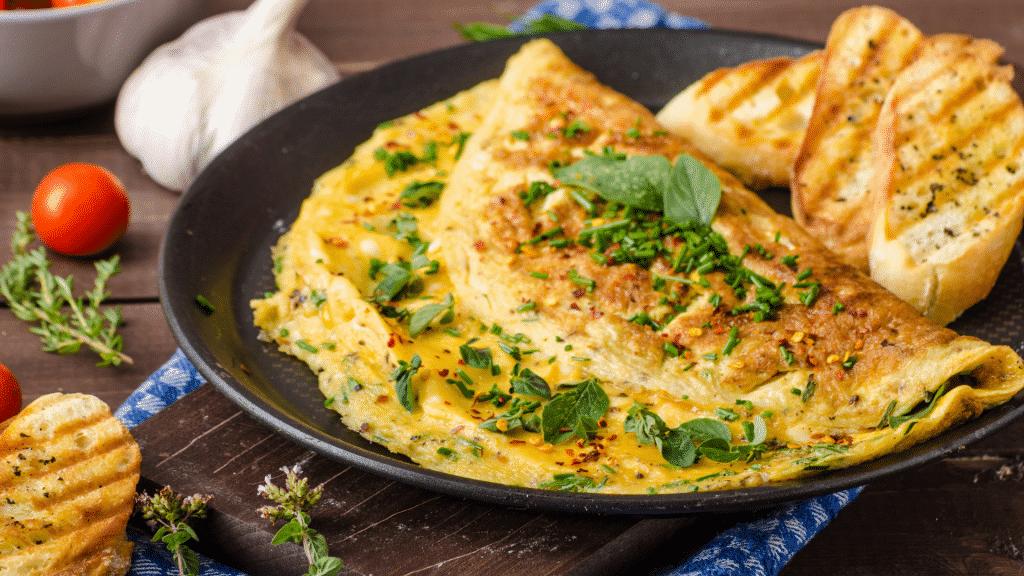 Prato com omelete, torradas e ervas.