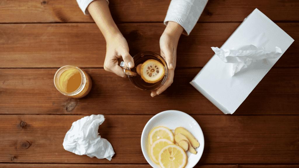 Ingredientes contra a gripe sobre uma mesa, além de lenços de papel e uma pessoa segurando uma xícara de chá